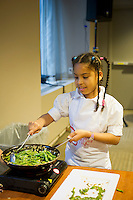 A young chef cooks string beans.  Children participating in Nourishing NYC's Junior Chef program prepare a healthy Thanksgiving dinner in midtown in New York on Saturday, November 19, 2011.   © (Frances M. Roberts)