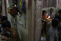 Artisanal gold smiths in Kolkata (Calcutta). These guys make about 3-400 USD a month at the top end.  They live in the workplace. At night they move the worktables aside and sleep on the floor and there are a few other places for them to crowd in to......