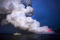 An illegal lava boat charter seems dangerously close to the flow as it reaches the ocean of the Big Island Coast.