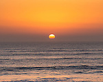The sun sets as a late autumn swell rolls in at Compton Bay on the Isle of Wight.