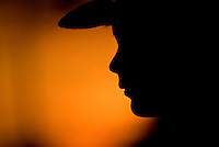 Young boy in cowboy hat silhouetted against setting sun
