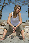 A beautiful young woman wearing a white tank top sits on a drift log at Cadboro Bay beach in Victoria, British Columbia, Canada.