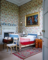 A painted lit bateau upholstered in pale blue fabric complements the floral wallpaper in this bedroom