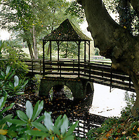 A gazebo at the centre of a wooden footbridge that crosses a small stream in the grounds of this country property
