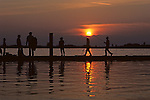 Family fishing silhouetted at sunset walking on boat pier Everett Washiongton State USA.