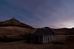 An abandoned homestead in Cascade County, Montana is seen near twilight with a mountain in the background.