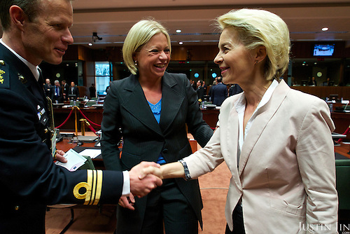 German defence minster Ursula von der Leyen meets an unidentified person at the EU Council. Dutch defence minister Jeanine Hennis-Plasschaert is in the middle.