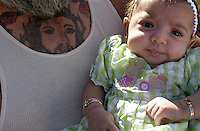 Three-month-old Savannah Martinez rests in the arms of grandfather Dennis Chavez Fridays, as pilgrims to the Santuario de Chimayó in New Mexico file through the doors of the 185-year-old adobe church. The annual Holy Week pilgrimage can draw up to 10,000 penitents on Good Friday alone.