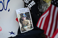 Phoenix, Arizona. July 3, 2013. A small makeshift memorial for the 19 Arizona firefighters who died on June 30 battling the Yarnell Hill wildfire was built outside the Forensic Science Center in Phoenix, where autopsies are being conducted. The photograph of 21-year old Kevin Woyjeck is seen near an American flag to pay tribute to him and the other 18 firefighters who died on Sunday, June 30, 2013 in Arizona. His father, Joe Woyjeck, was a captain with Los Angeles County Fire. Photo by Eduardo Barraza © 2013