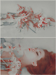 Young adult female with red hair and flowers lying with eyes closed.This image contains grain and texture.