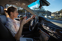 Female driver drinks coffee with cigarette in hand during commute in Austin, Texas traffic jam.