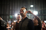 An assistant ties a face mask on a model for the Brazilian brand, Lino Villaventura, backstage at São Paulo Fashion Week for Summer Season 2013/2014, at Bienal, in Ibirapuera Park, São Paulo, Brazil, on Friday, March 22, 2013.