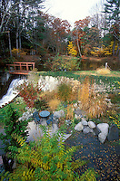 Creating a view that looks good from above or from a window: Ornamental grass backyard garden in autumn fall with bridge, waterfall, trees, shrubs, patio, viewed from above, furniture table and chairs, rock boulders, tree foliage