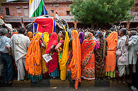 Colorful Rajasthani women watch at the Teej Parade passed by.