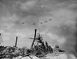 Five carrier-based planes fly over a group of Marines headed for the north end of Namur Island. The bombing of the island continued after the Marines landed and it took them just 24 hours to capture the entire island.