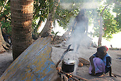 Cooking dinner, a meal of taro, on Han Island, Carterets Atoll, Papua New Guinea, on Monday, Dec. 11, 2006.   Rising sea levels have eroded much of the coastlines of the low lying Carteret islands (situated 80km from Bougainville island, in the South Pacific), and waves have crashed over the islands flooding and destroying what little crop gardens the islanders have. Food is in short supply, banana and swamp taro crops are failing due to the salt contamination of the land, and the islanders live on a meagre one meal per day diet of fish and coconut. There is talk by the Autonomous Region of Bougainville government to relocate the Carteret Islanders to Bougainville island, but this plan is stalled due to a lack of finances, resources, land and coordination.