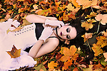 A girl with pale skin and long black hair in a white dress lying in colorful autumn leaves.