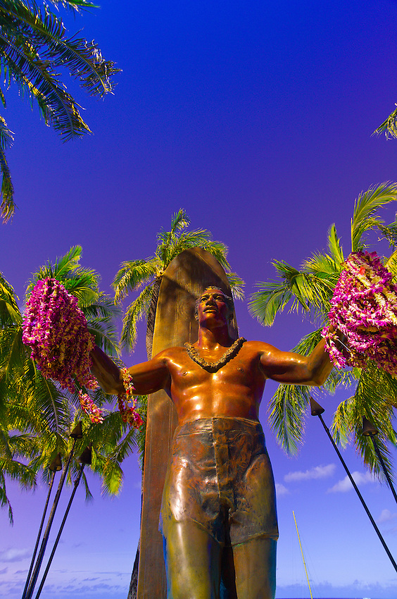 Statue of famous surfer Duke Kahanmoku holding leis on Waikiki Beach, Honolulu, Oahu, Hawaii, USA