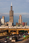 As a Pink Line El train passes high overhead, traffic flows into the city of Chicago on the Eisenhower Expressway as the Sears Tower looms.