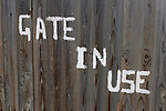 On a house's wooden garage gates the words Gate in Use have been painted by hand in white on wooden gates in a quiet suburban London street.