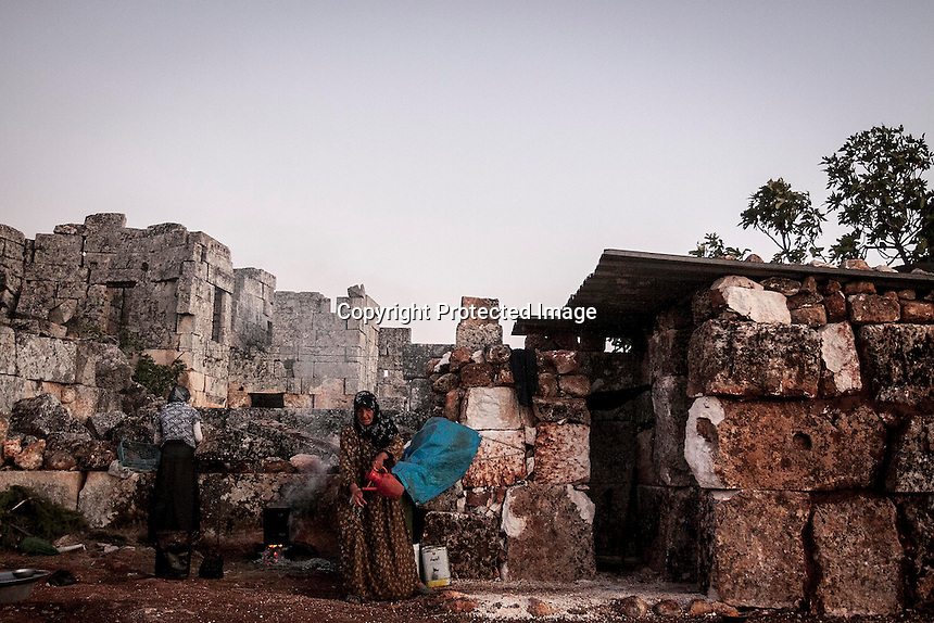 """In this Thursday, Sep. 26, 2013 photo, a Syrian displaced family cook a meal for dinner at the Kafr Ruma, an ancient roman ruins used as temporary shelter by those families who have fled from the heavy fighting and shelling in the Idlib province countryside of Syria. Dozens of families settled in the ancient ruins known as """"The Forgotten City"""" and declared human heritage by UNESCO, when the clashes between opposition fighters and government forces broke out in the region since more than two years ago. (AP Photo)"""