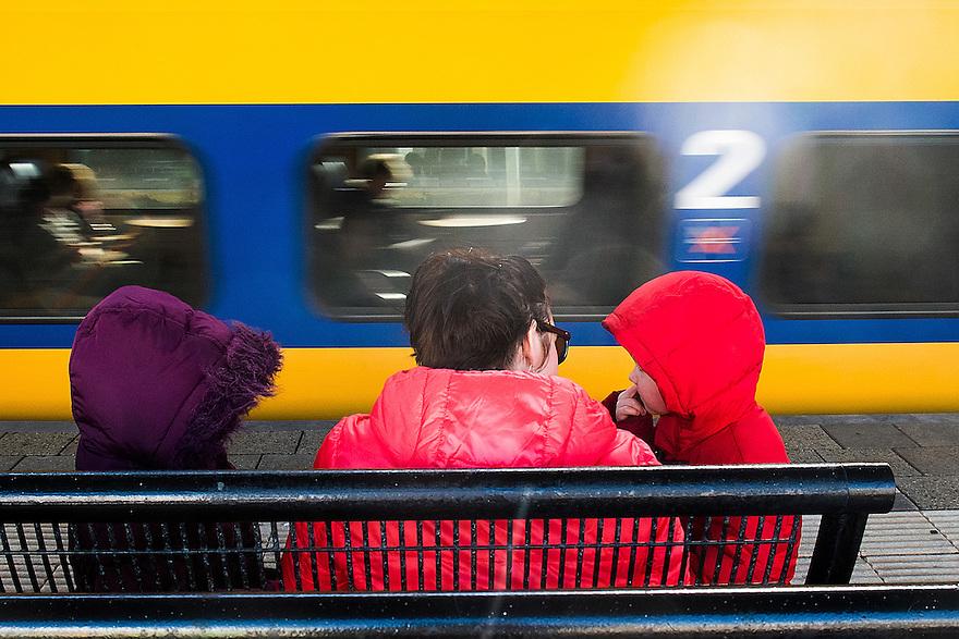 Nederland, Driebergen, 21 feb 2014<br /> Moeder met twee kleine kinderen op het perron van ns-station. Een sneltrein raast voorbij.<br /> <br /> Foto(c): Michiel Wijnbergh