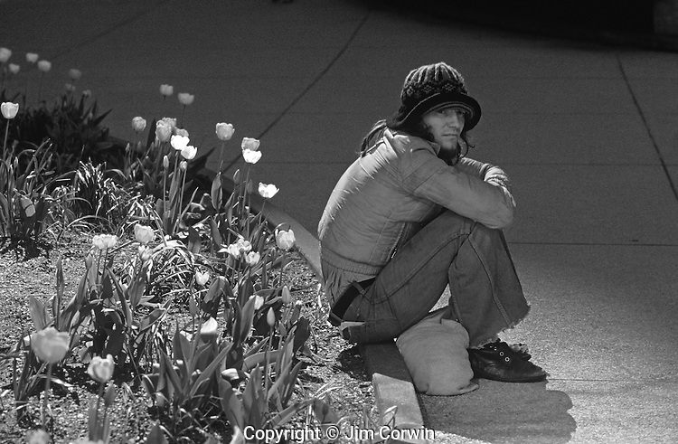 Man sitting along  curb by flower garden downtown Seattle
