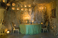 A romantic table for two stands in this grotto dining room and is lit by a series of scattered candles and tealights