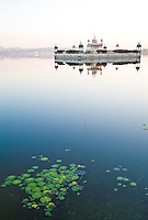 A tranquil lake setting with a temple and lilies in the foreground.<br /> (Photo by Matt Considine - Images of Asia Collection)