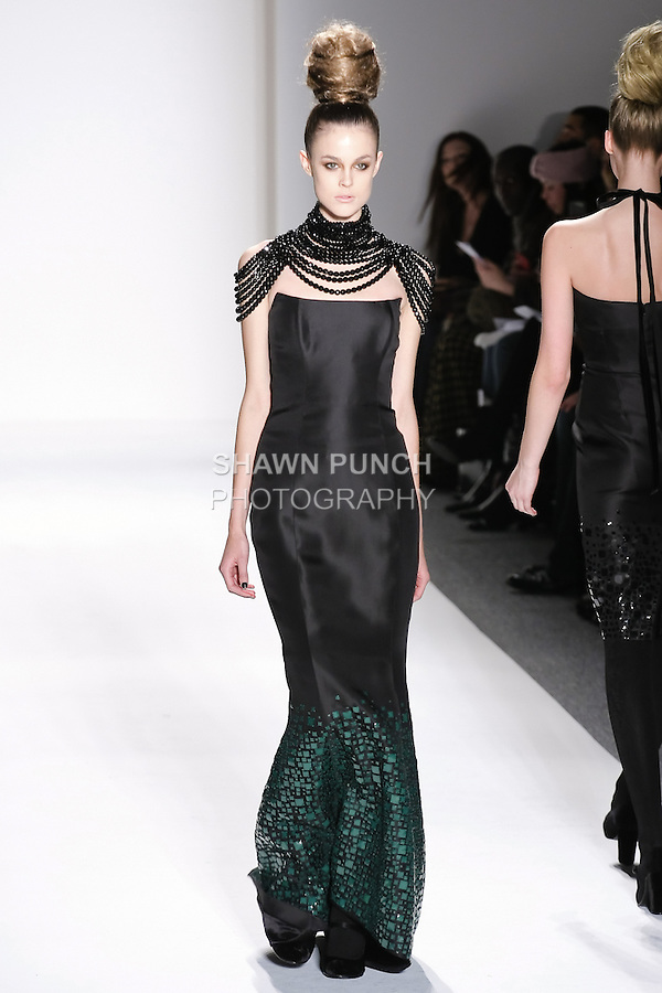 Model walks runway in a black jet beads draped heiress necklace, black silk gazar strapless gown w/confetti of emerald square sequins, from the Zang Toi Fall 2011 Timeless Beauties collection, during Mercedes-Benz Fashion Week Fall 2011.