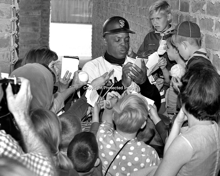 San Francisco slugger Willie Mays signs autographs for a group of youngsters at Casa Grande, Arizona in 1967.
