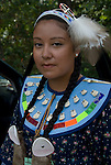 Portrait of young Native American female dressed in her pow wow regalia. Examples of ethnic pride, heritage, celebration, and traditional folk art crafts.