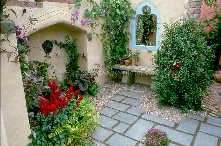 Outdoor Room: Courtyard garden with flagstone bluestone Slate patio with masonry walls and medieval window style, inset water feature, open window, red Astilbe, clematis red and purple climbing vines, herb thymes Thymus in bloom in stepping stone crevices, ferns, garden bench made of stone, inset wall, Mediterranean style, walled enclosed sense of privacy, secret and hidden lovely and pretty and varied garden design