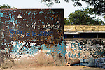 "The word ""squeezing"" is seen on a wall above a patient asleep in the enclosed yard of a men's ward at the Accra Psychiatric Hospital."