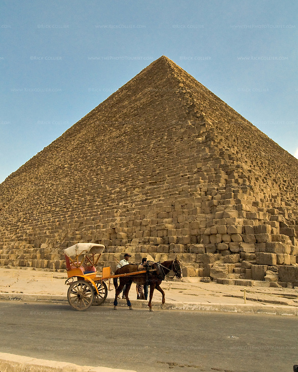 """Giza, Cairo, Egypt -- A horse-drawn carriage """"taxi"""" waits for a tourist rider in the shadow of the Great Pyramid of Khufu (Cheops). © Rick Collier / RickCollier.com."""