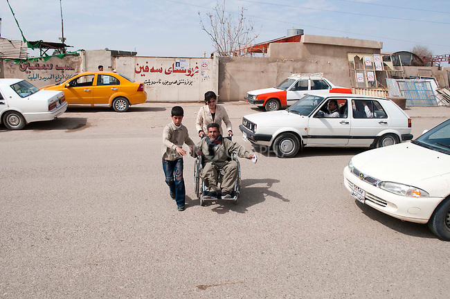 KIRKUK, IRAQ: Children wheel their disabled father across the street to the polling station...Residents of the city of Kirkuk vote for the first time.  Because of violence in the ethnically mixed city, Kirkuk was excluded from the 2005 elections...Photo by Kamaran Najm/Metrography