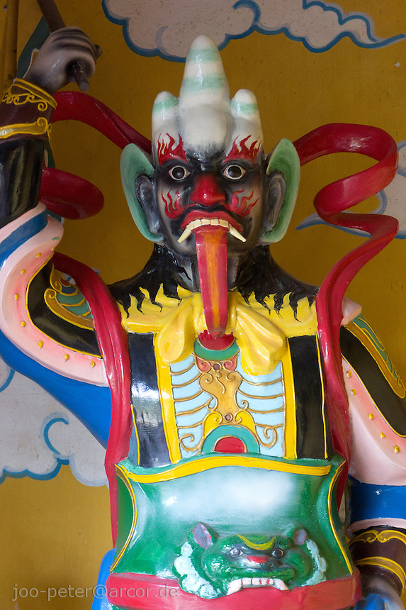 guarding demon spirit  on left side of the entrance of atemple in  the city Hoi An, Vietnam
