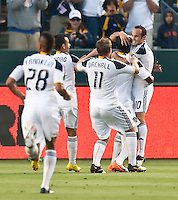 LA Galaxy players Sean Franklin (28), Juninho (19), Chris Birchall (11) and Landon Donovan (10) engulf Edson Buddle (14) after his goal during the first half of the game between LA Galaxy and the Seattle Sounders at the Home Depot Center in Carson, CA, on July 4, 2010. LA Galaxy 3, Seattle Sounders 1.
