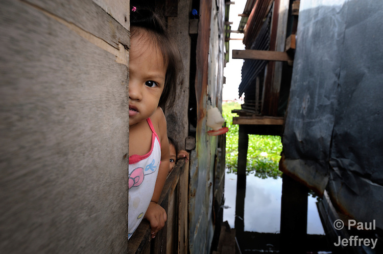 A girl and her little sister look out the window of their home in Santa Cruz, Laguna, in the Philippines. Residents here have been subjected to increased flooding from the Laguna de Bay in recent years, and with the help of the ACT Alliance are organizing to look for alternatives.