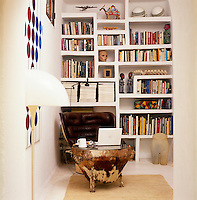 A built-in bookcase houses an eclectic assortment of objects, books and DVD's and a large animal skin drum is used as a table
