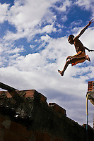 Afro-Brazilian adolescent practices sport in a Rio de Janeiro favela, jumping from one house to another one - daily life at Favela da Mare.