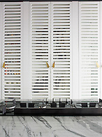 The wall of the open plan kitchen is lined with latticed wooden doors which disguise kitchen shelves and storage