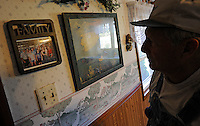 Caption 3<br /> Randell passes a family photo in his kitchen on September 25, 2013.