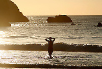 A girl exits from the surf at the Grand Plage beach in Biarritz, France, at susnset.