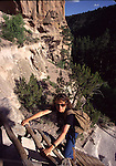 woman hiking on ladder at Bandelier NM, Alcove House