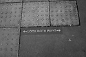 London, UK. 04.04.2015. Look Both Ways sign on the pavement, East London. Photograph © Jane Hobson.