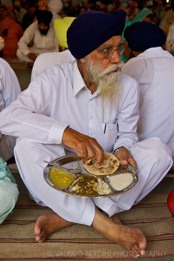 A man enjoys his meal. To enter the Golden Temple area is mandatory to have the head covered and remove your shoes.  It is also strictly forbidden to bring alcohol, cigarettes and lighters.