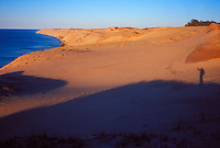 A backpacker's shadow is seen with the Grand Sable Dunes at dusk in Pictured Rocks National Lakeshore near Grand Marais, Mich.