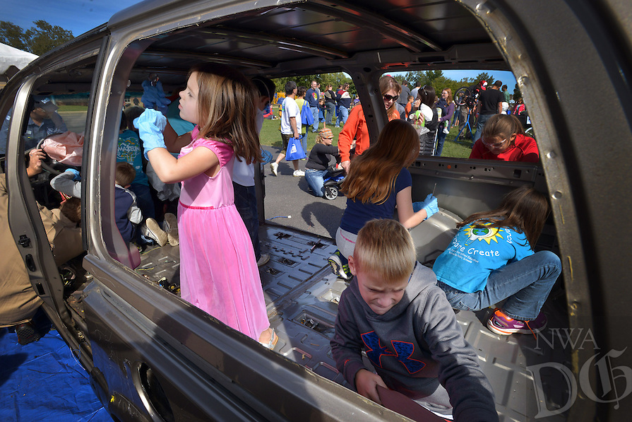 STAFF PHOTO BEN GOFF  @NWABenGoff -- 10/04/14 Audrey Johnson, 4, left, of Springdale and Caden Newell, 8, of Bentonville work on removing seat belts in the 'Car Take-Apart' during the Amazeum's inaugural Tinkerfest at Old High Middle School in Bentonville on Saturday October 4, 2015. George Nunnally Chevrolet in Bentonville donated the used minivan for children to strip to the frame during the event.