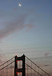 The crescent moon rising over the Golden Gate Bridge after sunrise In San Francisco, California.